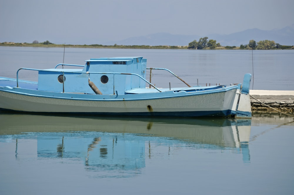 white and blue boat on water during daytime