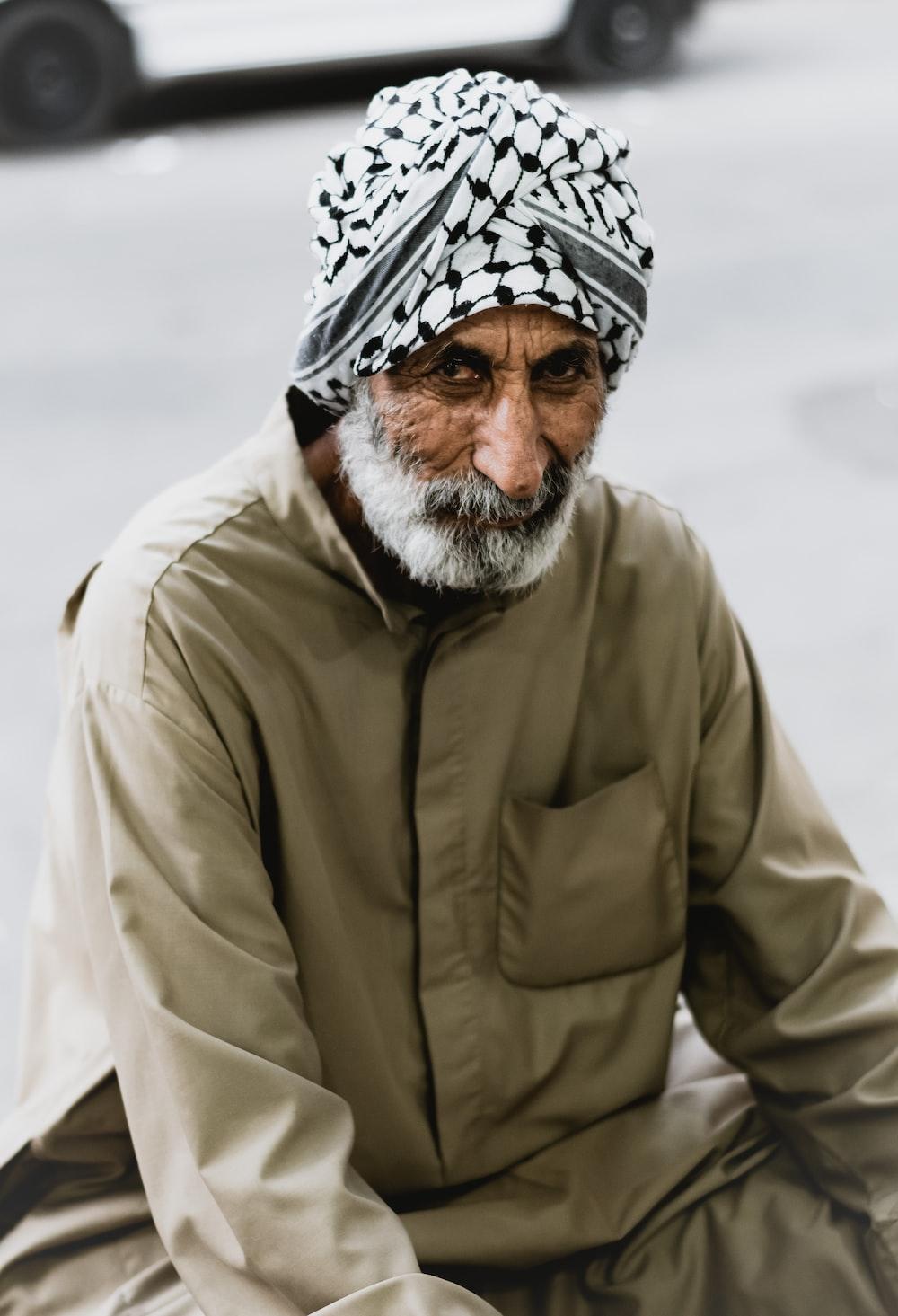 man in brown jacket wearing white and black bandana