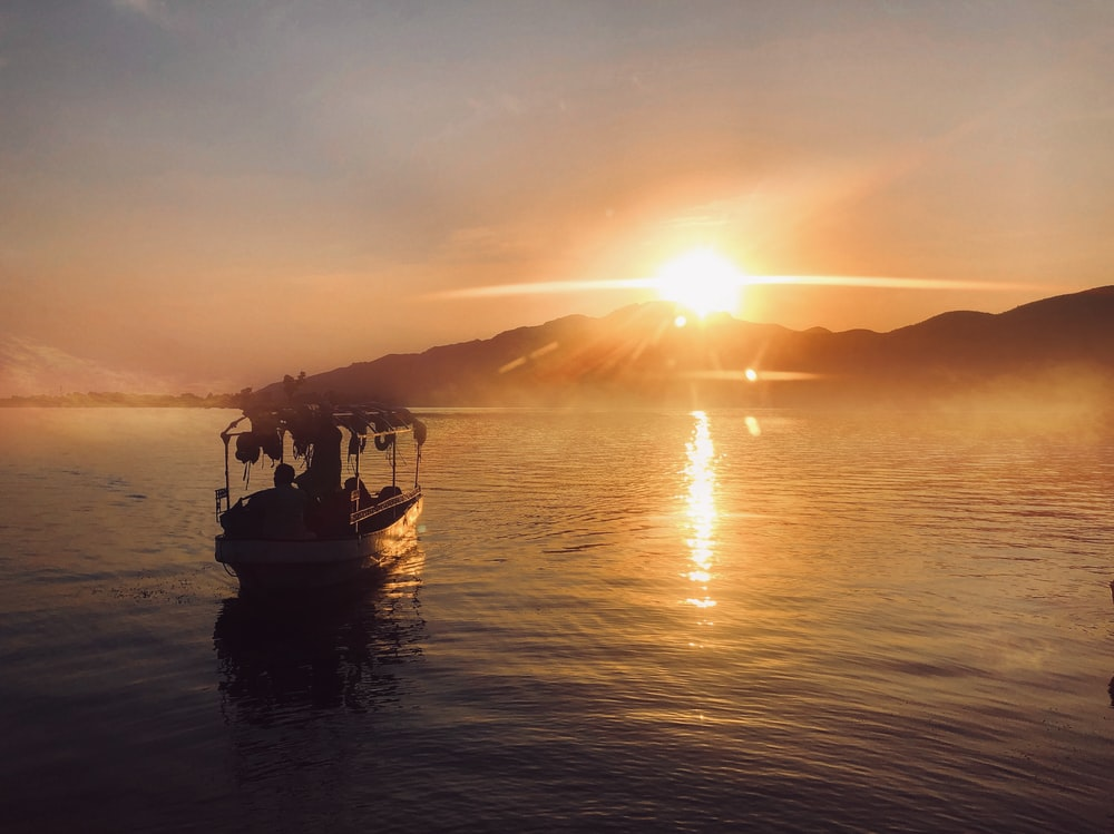 silhouette of people riding boat on sea during sunset