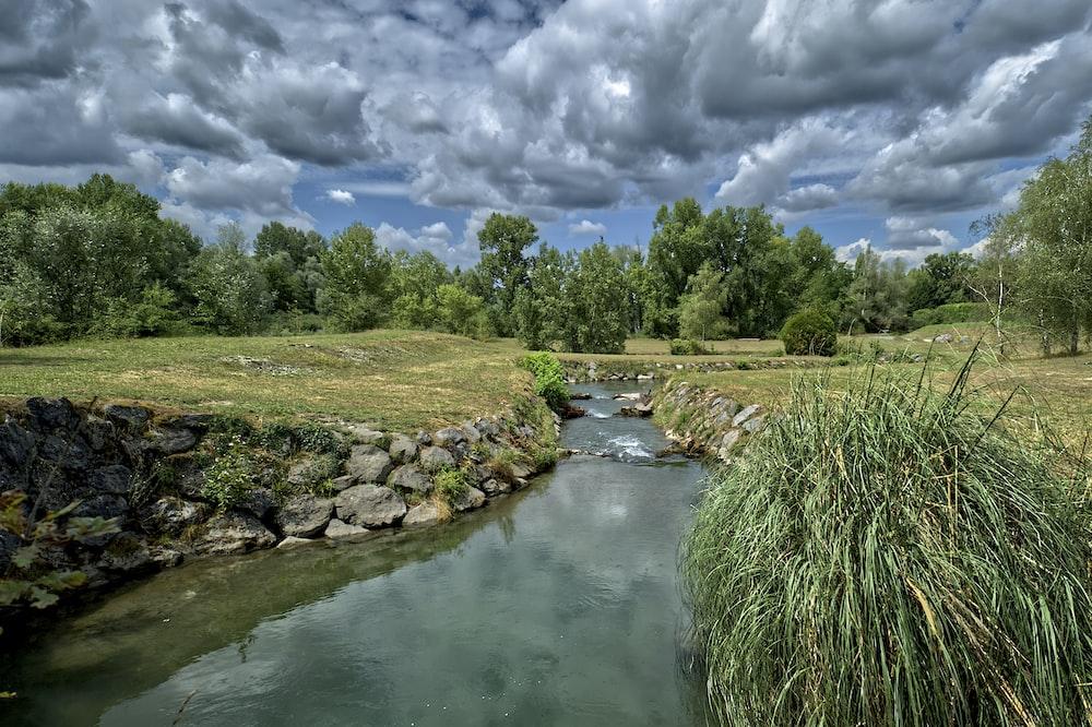 green grass field near river under white clouds during daytime