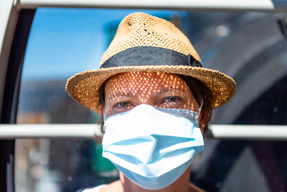 woman in brown hat with white face mask