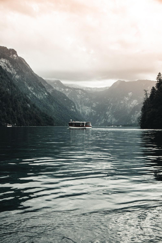 white boat on lake near green mountains during daytime
