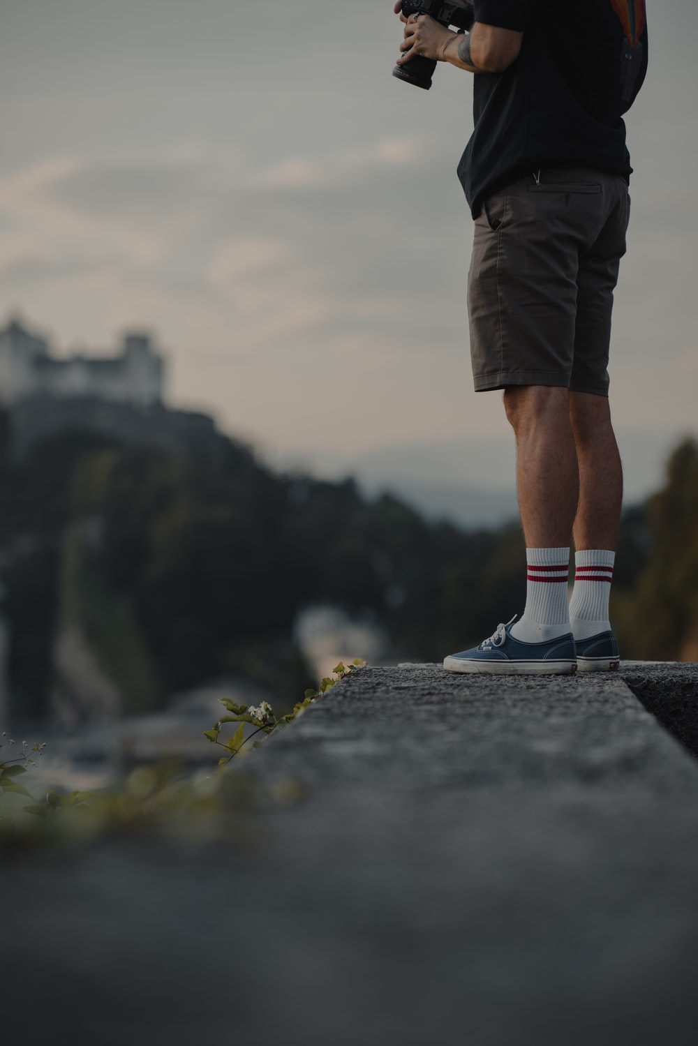 person in black shorts and white and black nike sneakers standing on gray concrete pavement during