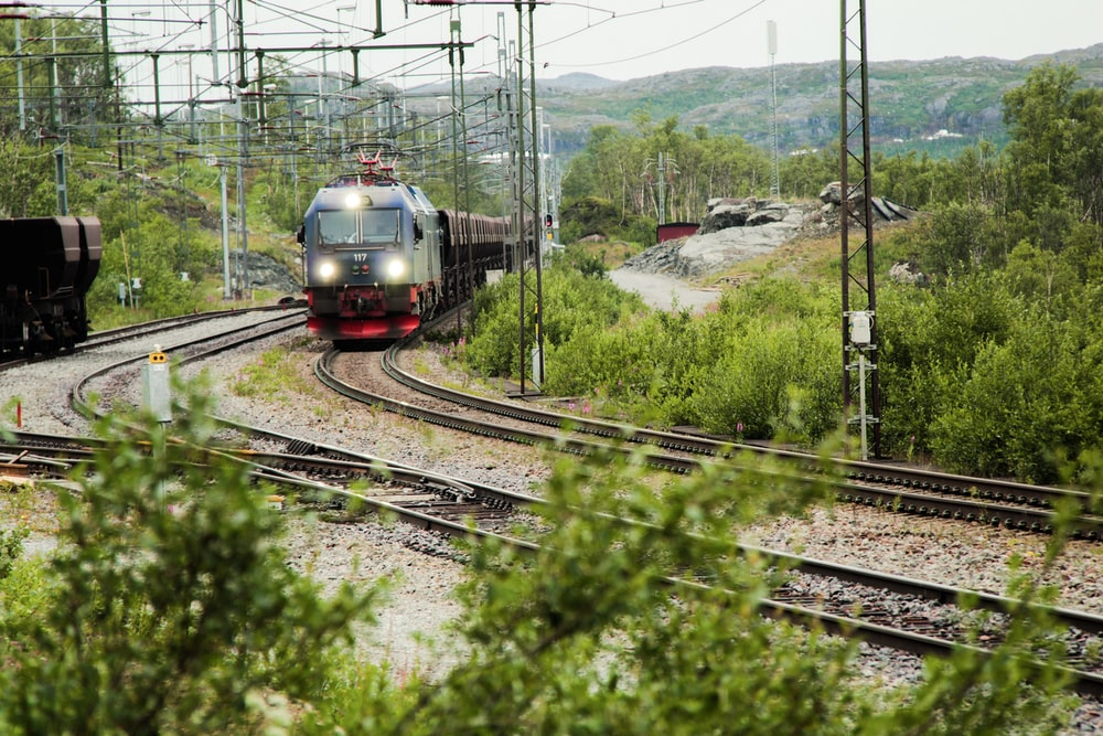 green and red train on rail tracks during daytime