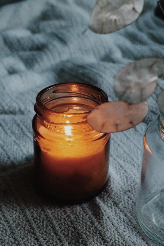 orange candle in clear glass jar