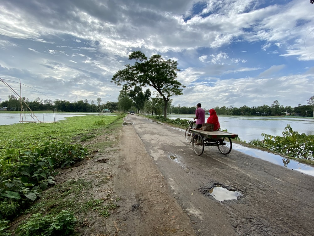 man in red shirt riding on bicycle near body of water during daytime