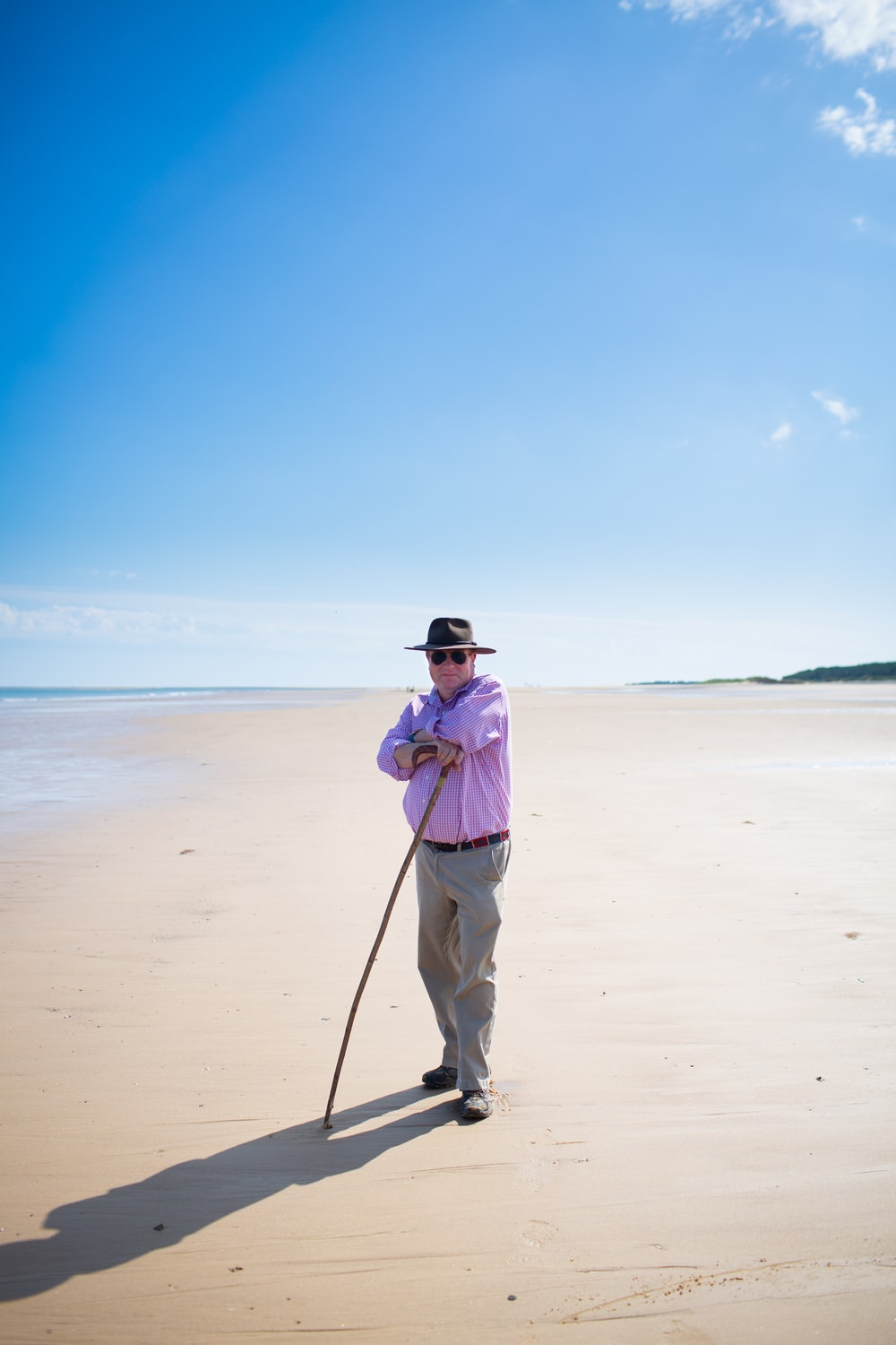 woman in purple dress shirt and white pants standing on beach during daytime