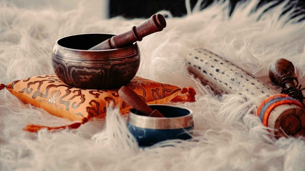 brown wooden mortar and pestle on white textile