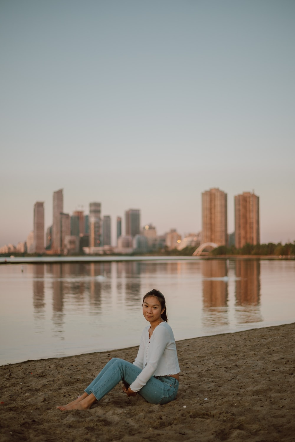 woman in white long sleeve shirt sitting on gray concrete bench near body of water during