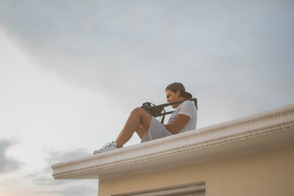 man in black t-shirt and blue denim shorts sitting on white concrete wall during daytime