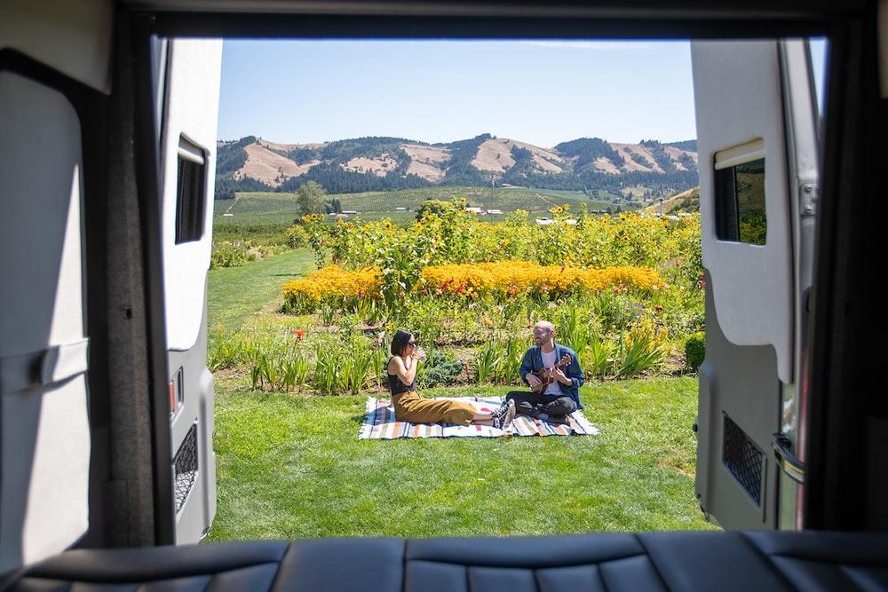 2 men sitting on green grass field during daytime