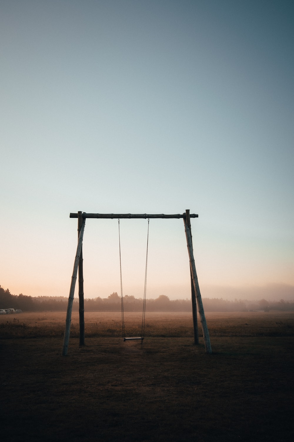 brown wooden swing under white sky during daytime