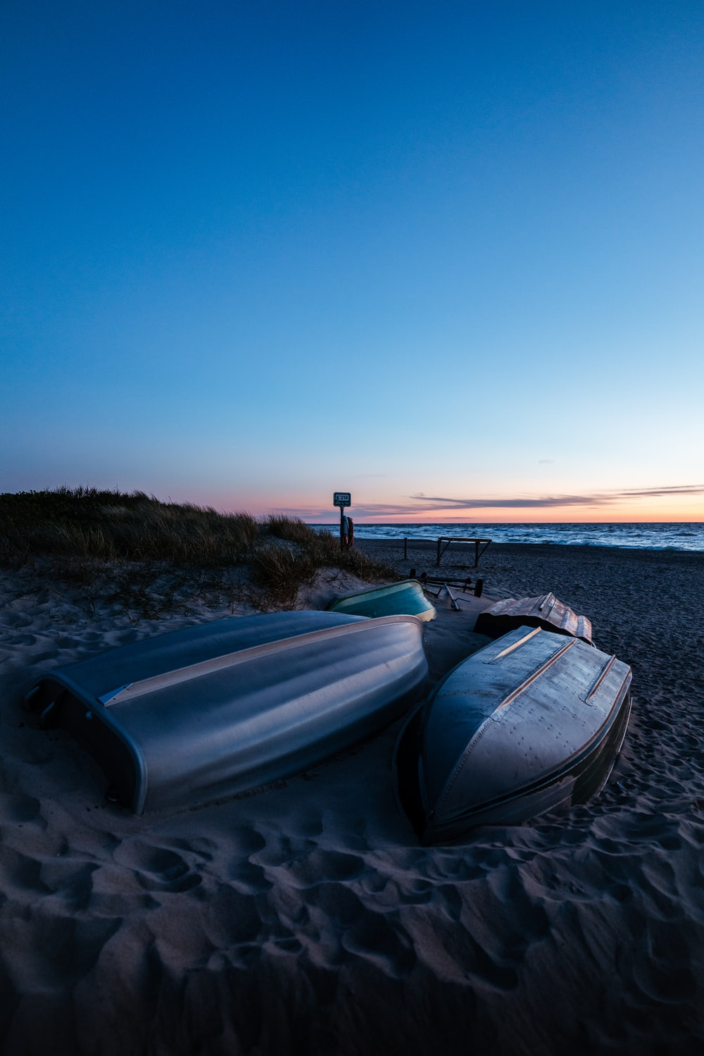 white and blue boat on sea shore during sunset