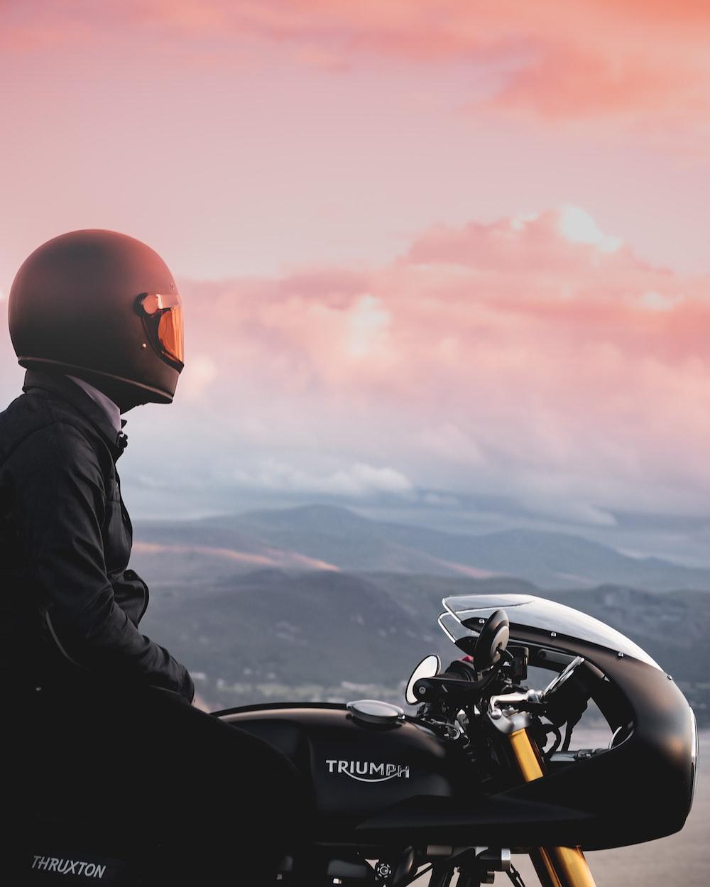 man in black jacket and orange helmet riding black motorcycle