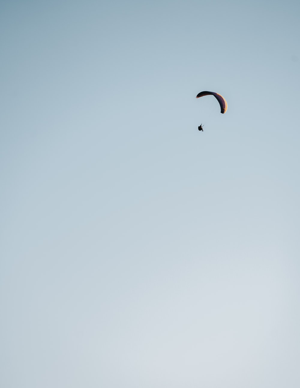 person in white shirt and black pants with white parachute in the sky