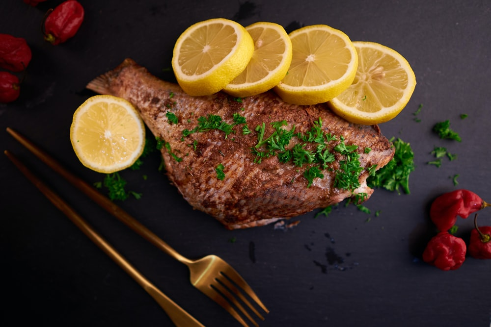 sliced lemon beside stainless steel fork on black wooden table
