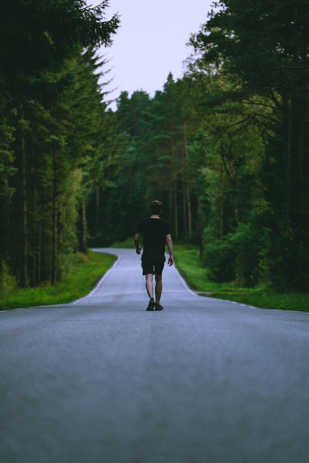 man in black t-shirt and black shorts walking on road during daytime