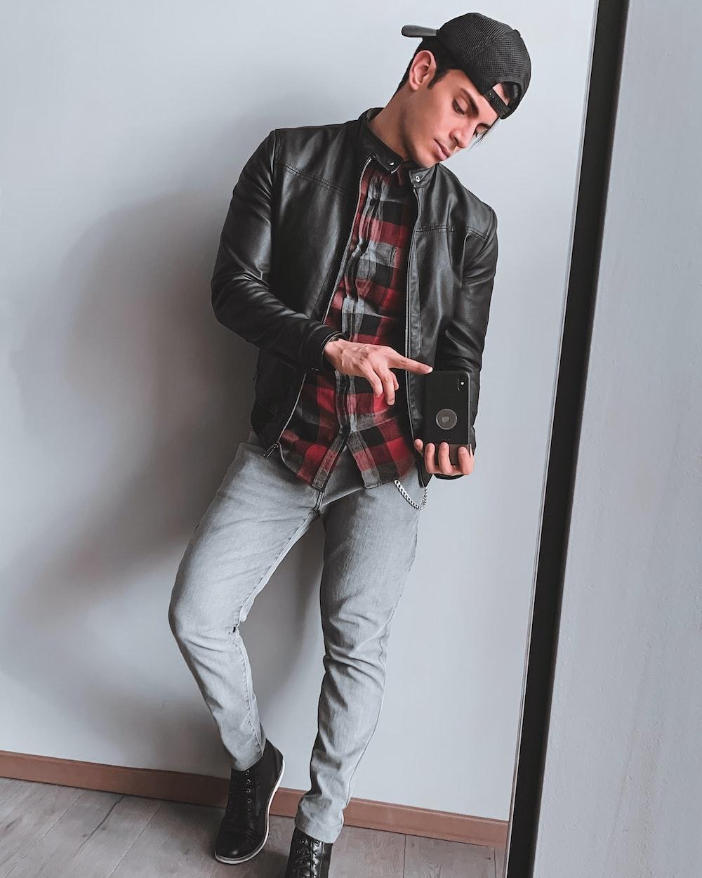 man in black leather jacket and blue denim jeans holding black smartphone