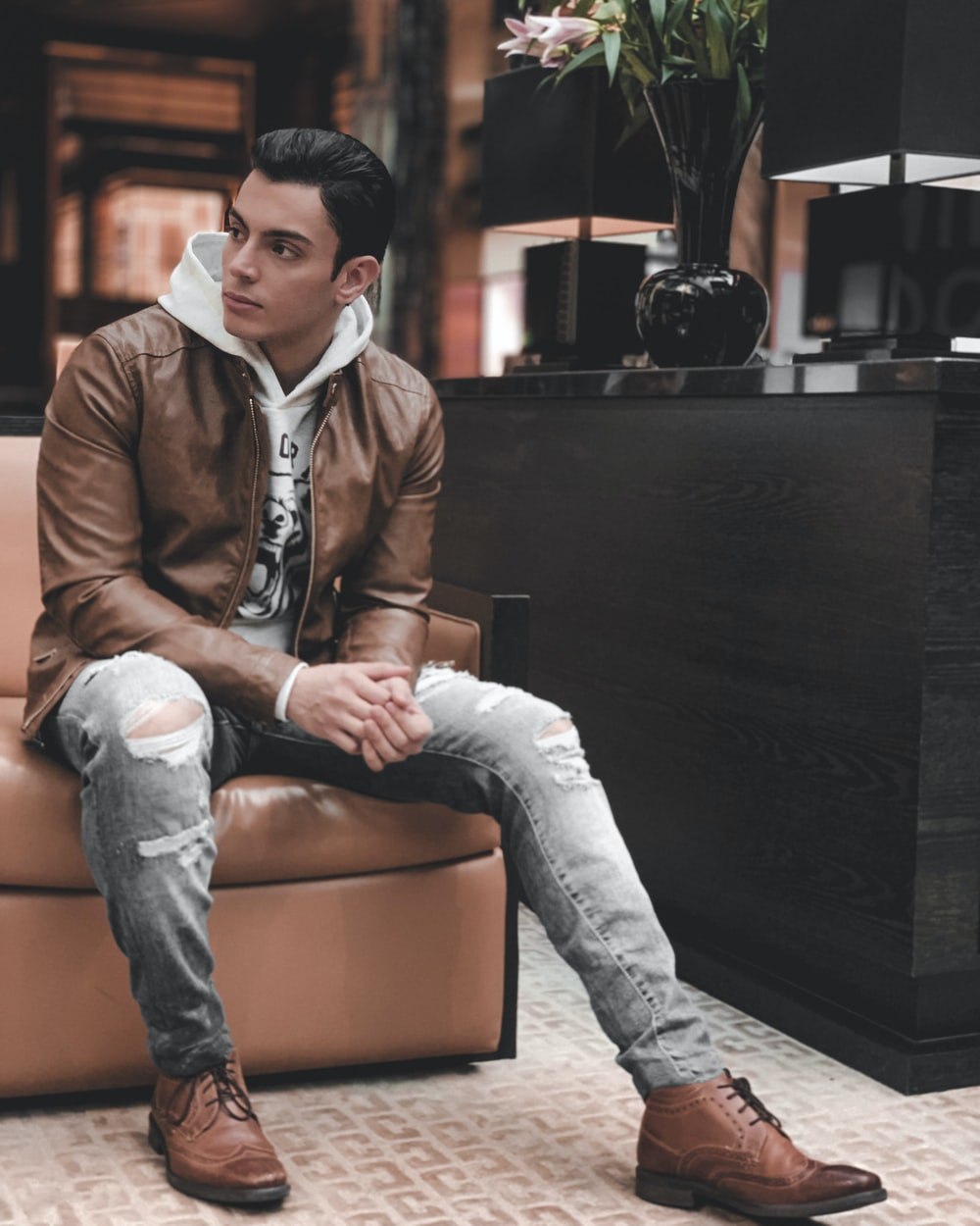 man in brown leather jacket sitting on brown leather couch