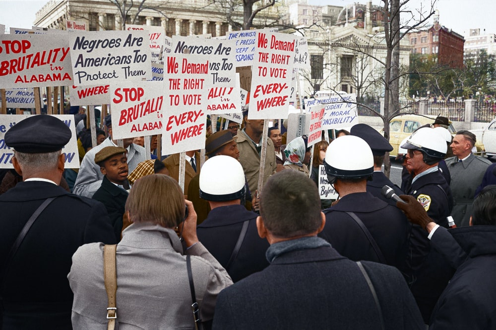 African American demonstrators outside the White House, with signs demanding the right to vote and protesting police brutality against civil rights demonstrators in Selma, Alabama