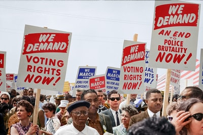 marchers holding signs demanding the right to vote at the march on washington colorized zoom background