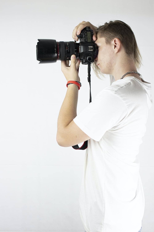 woman in white t-shirt holding black dslr camera