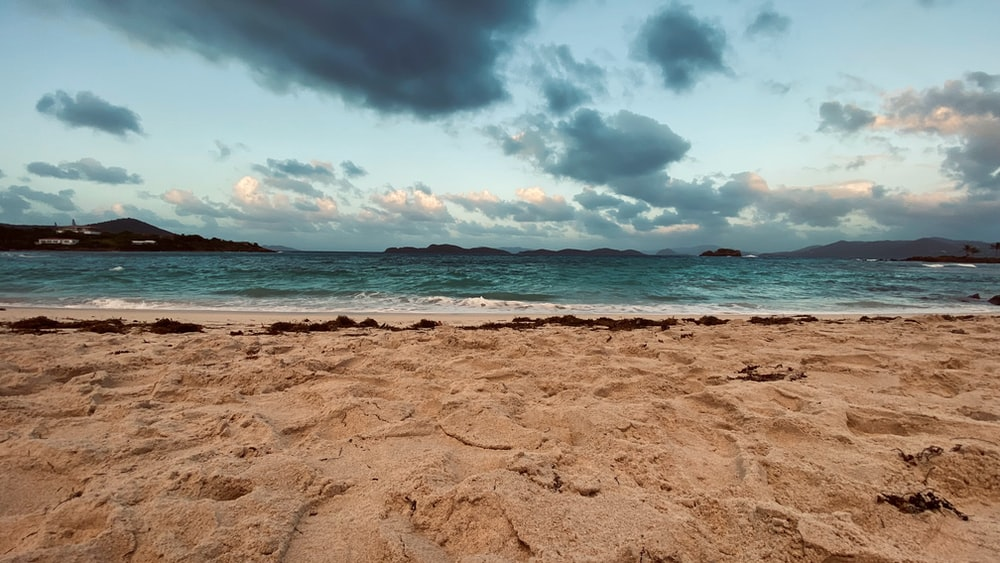 brown sand beach under cloudy sky during daytime