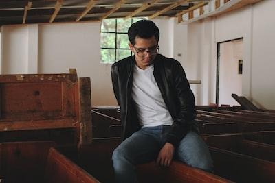 man in black leather jacket sitting on brown wooden bench pueblo revival teams background