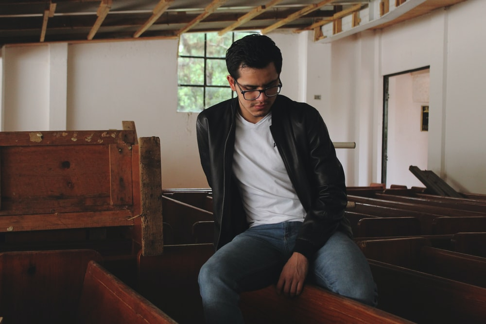 man in black leather jacket sitting on brown wooden bench