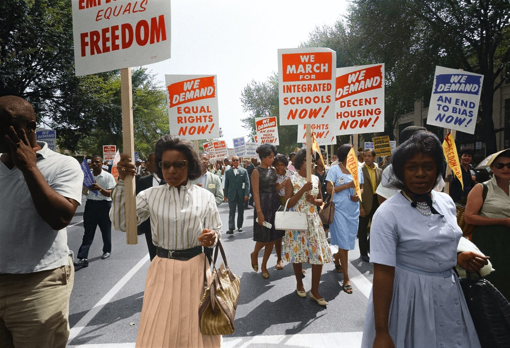 Demonstrators walk along a street holding signs demanding the right to vote and equal civil rights at the March on Washington
