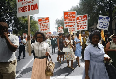 demonstrators walk along a street holding signs demanding the right to vote and equal civil rights at the march on washington colorized zoom background
