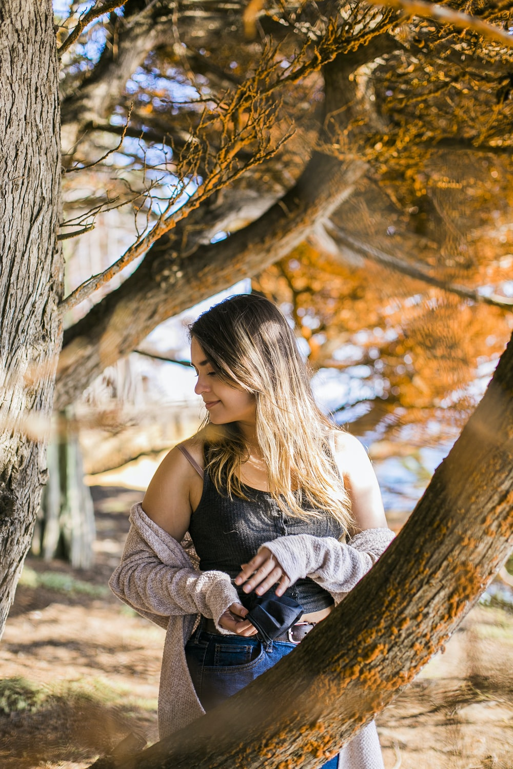 woman in black tank top and brown cardigan sitting on tree during daytime