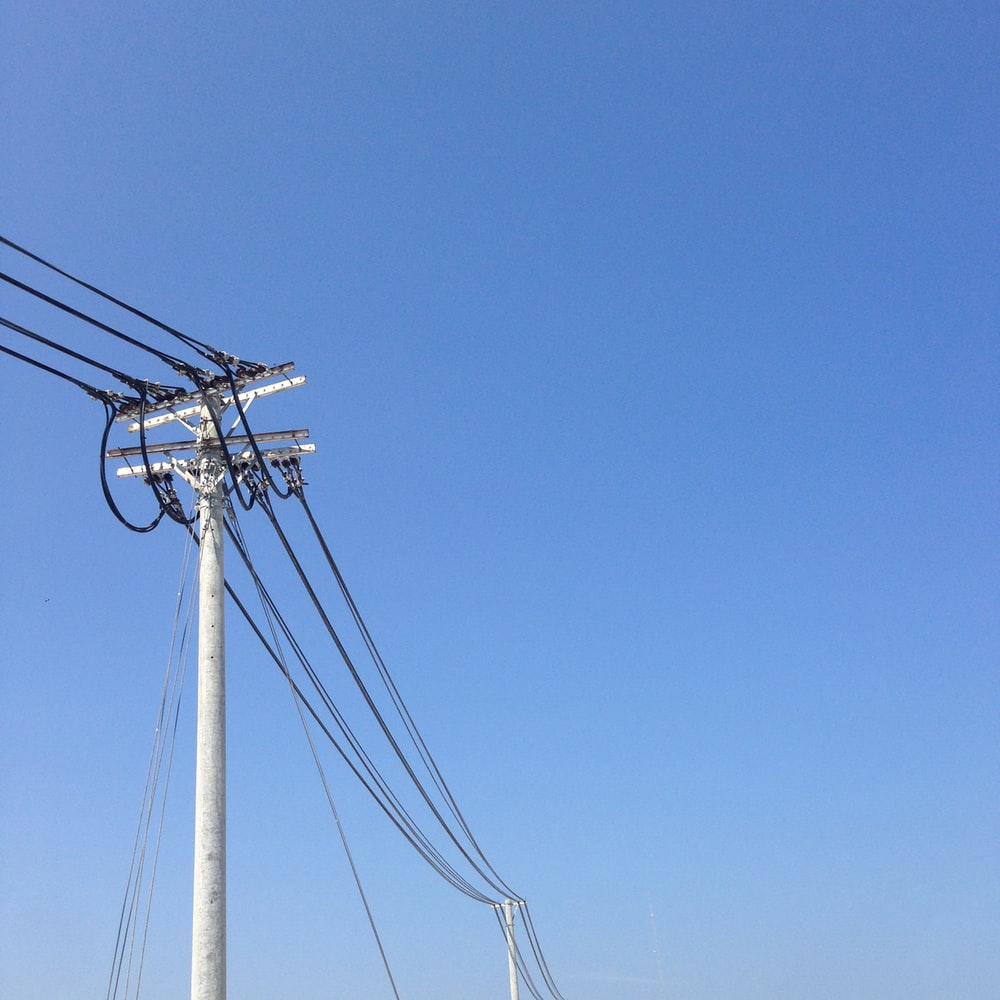 white electric post under blue sky during daytime