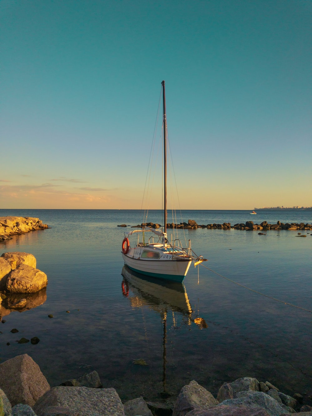 white and blue boat on sea shore during daytime