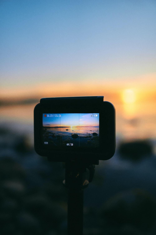 black dslr camera taking photo of sunset
