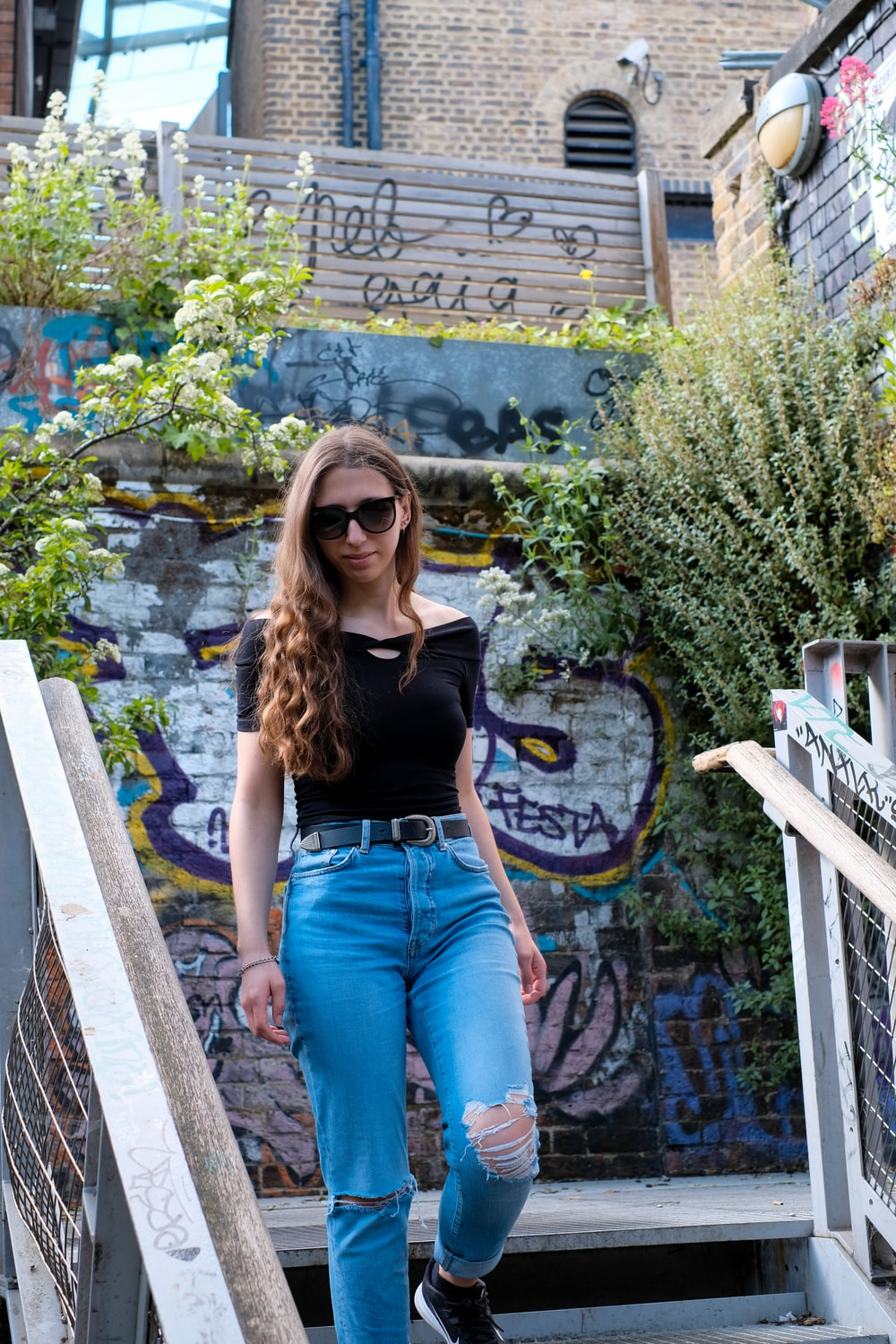 woman in black tank top and blue denim jeans sitting on brown wooden bench during daytime