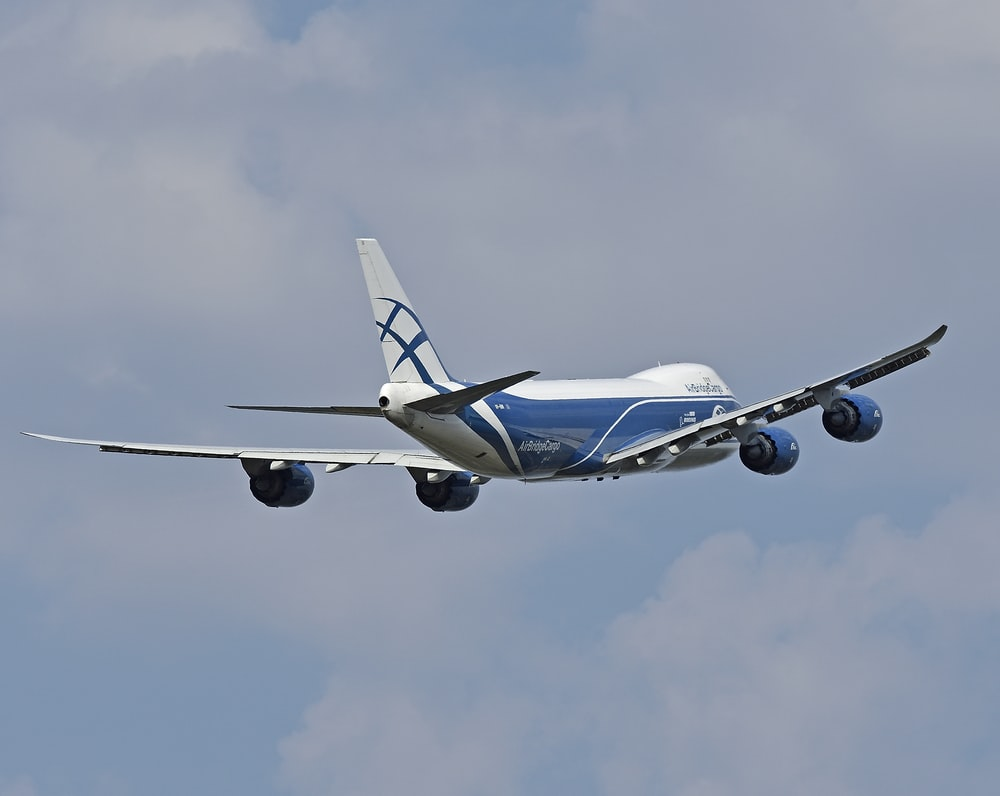 blue and white airplane in mid air during daytime