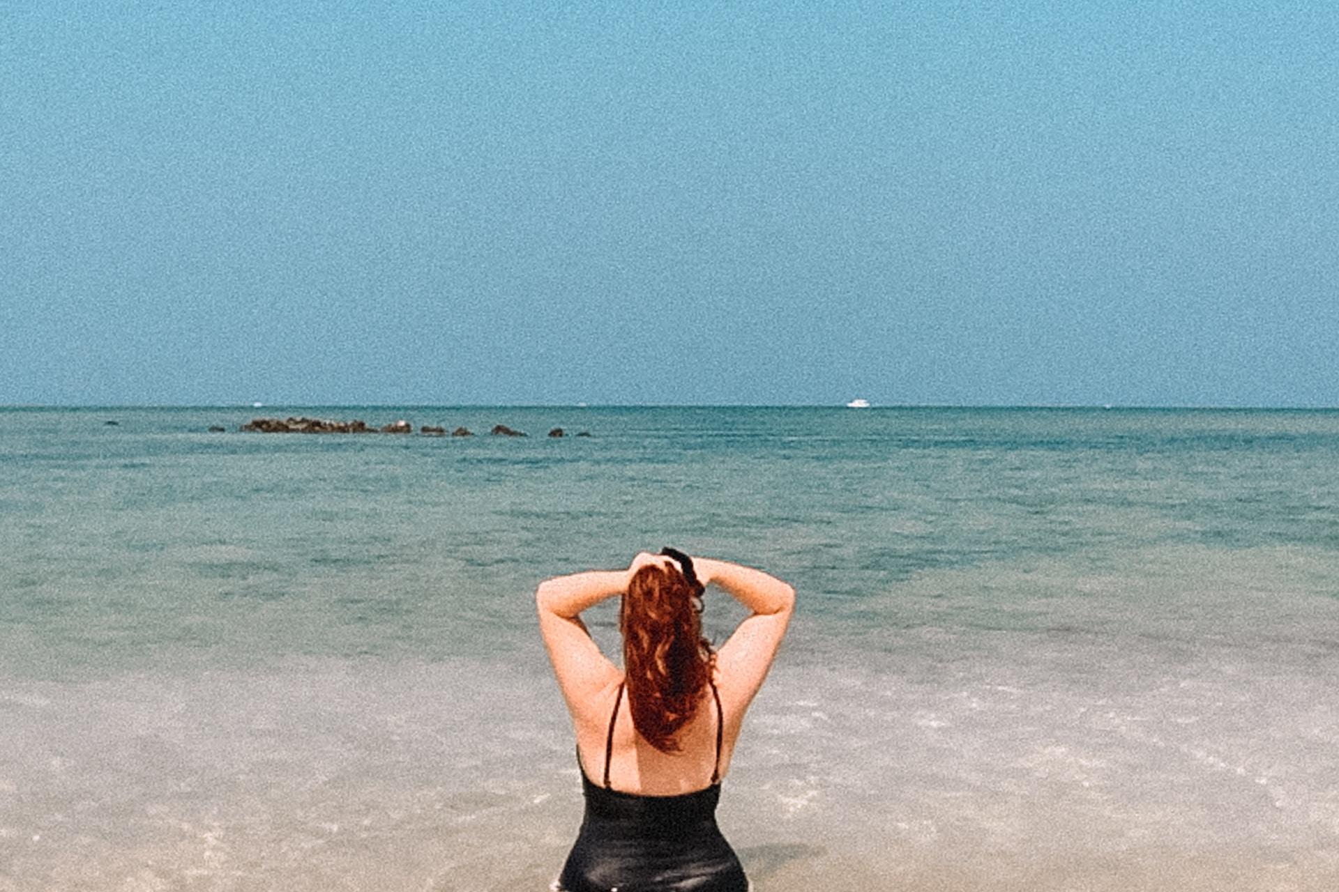 woman in black bikini lying on beach during daytime