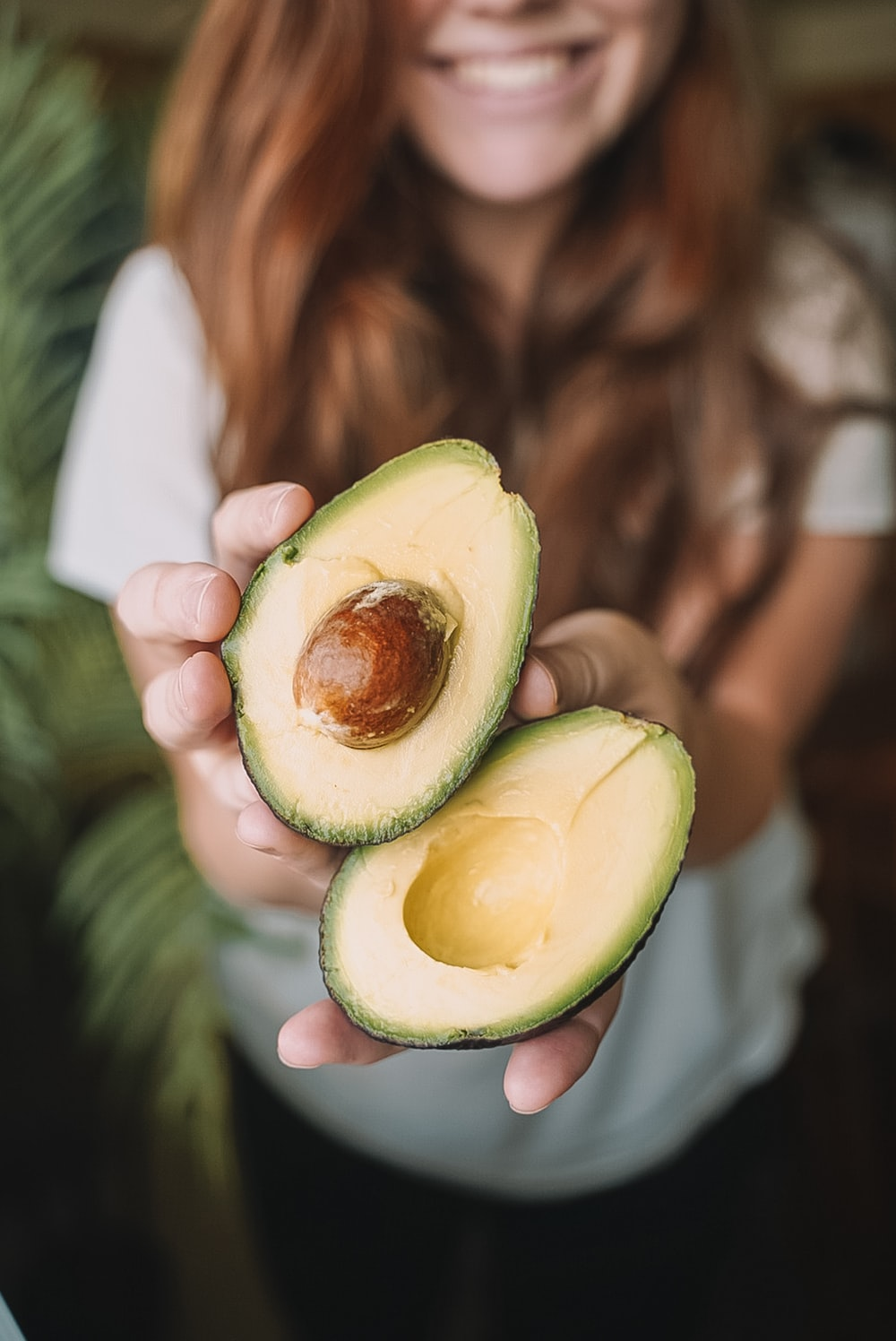 sliced avocado fruit on persons hand