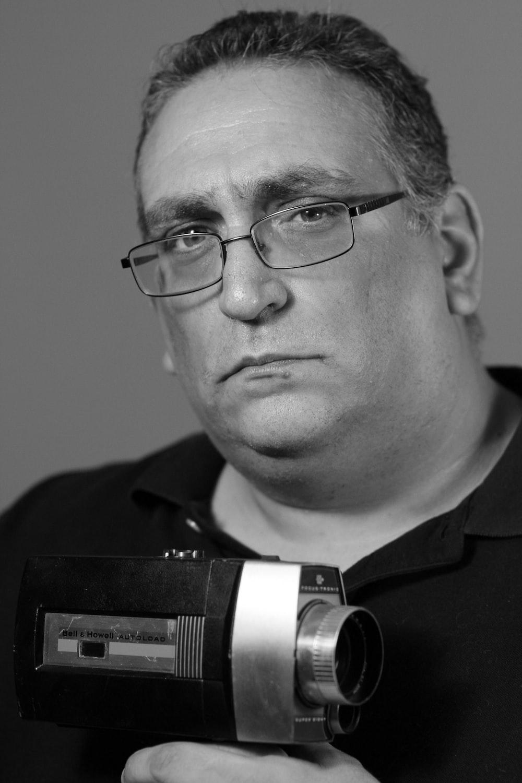 man in black framed eyeglasses holding camera
