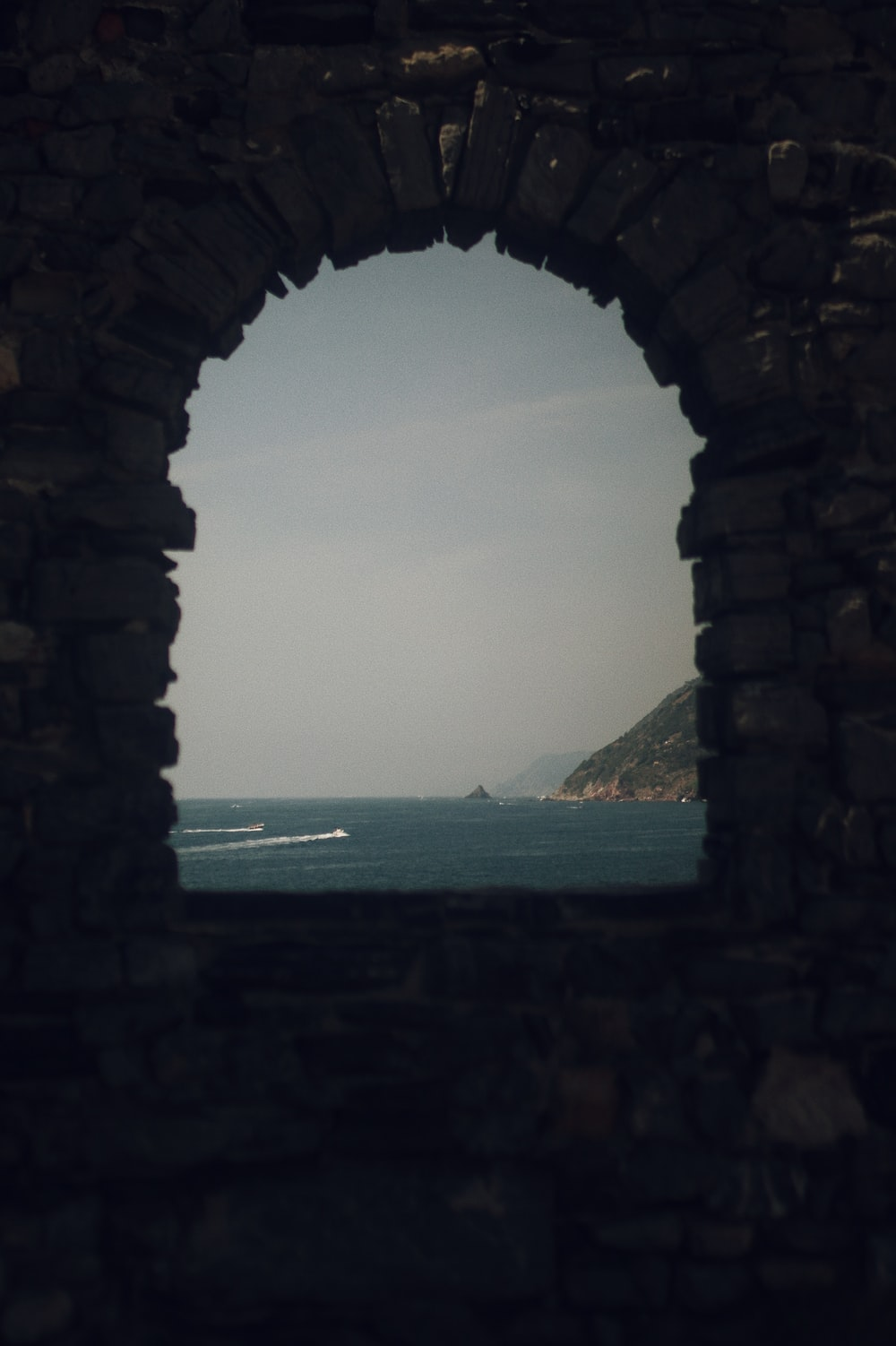 brown brick arch near body of water during daytime