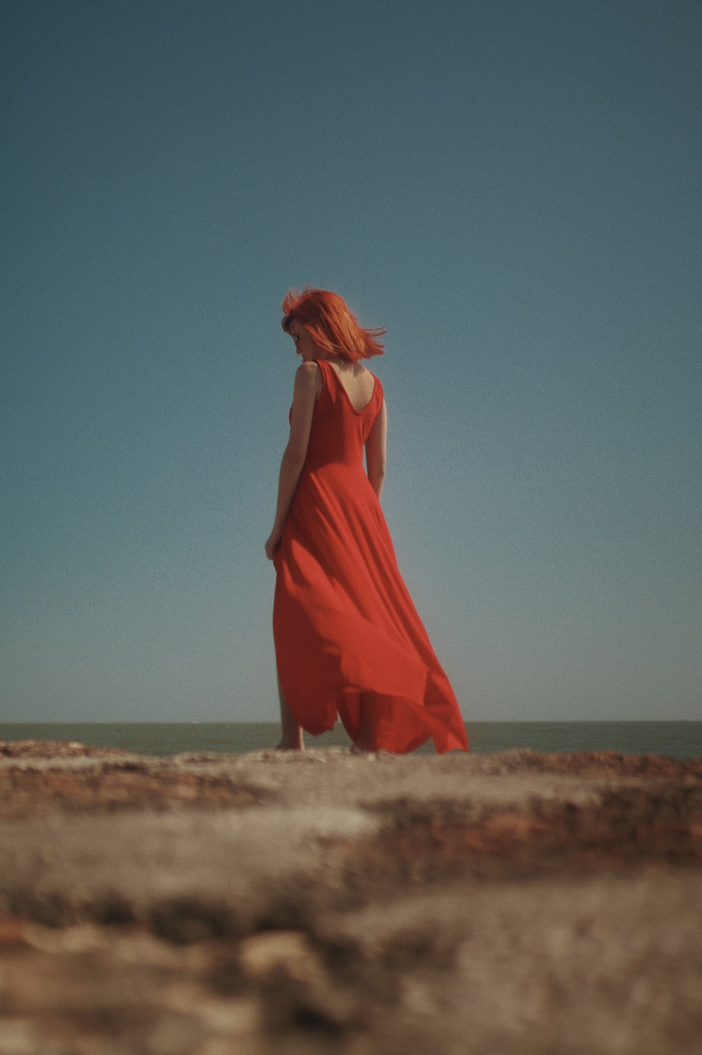 woman in orange dress standing on brown sand during daytime