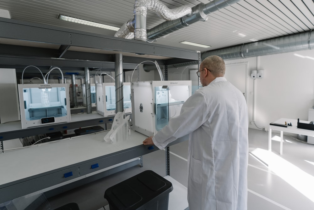 man in white laboratory gown standing near white and black machine