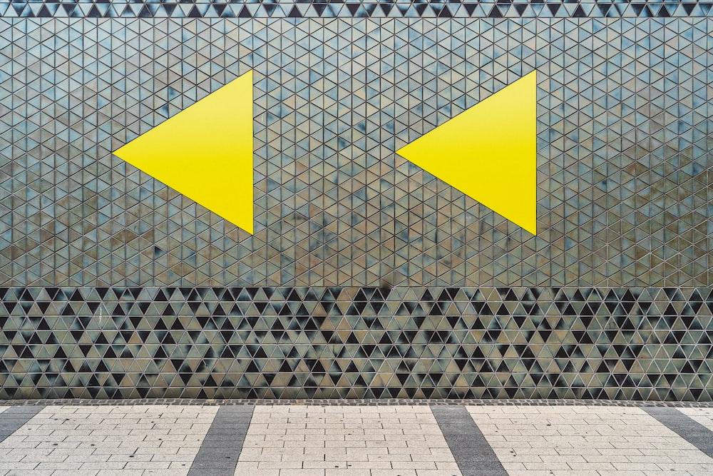 yellow and black arrow sign on grey concrete floor
