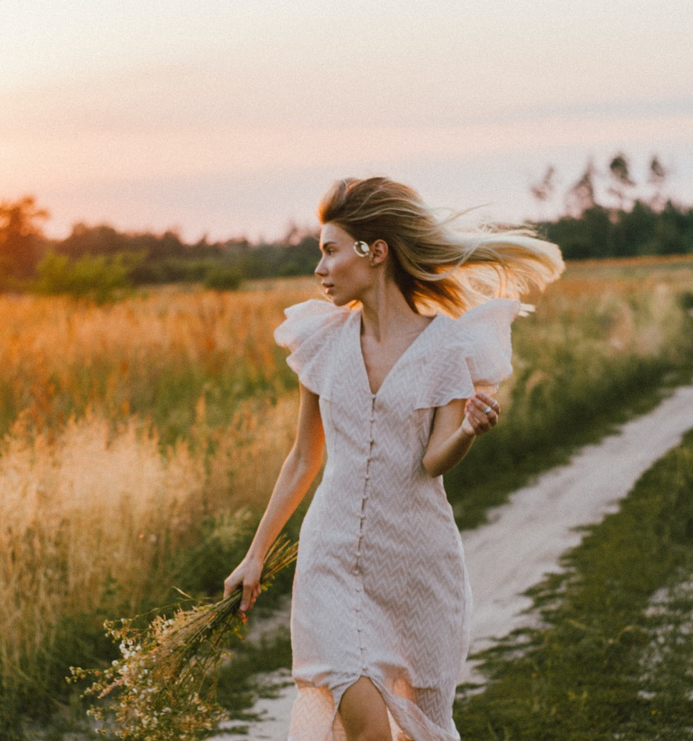 woman in white dress walking on green grass field during daytime