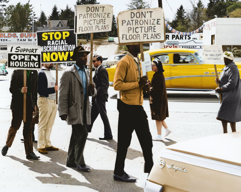 """Protestors hold signs reading """"Stop Racial Discrimination Now!"""" during a demonstration at Picture Floor Plans, Inc."""