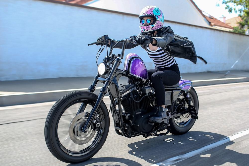 man in black and white jacket riding black motorcycle during daytime