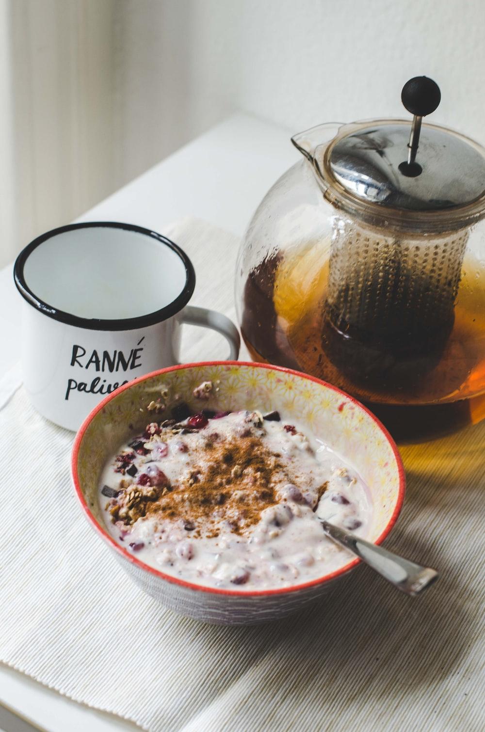 white ceramic mug beside white ceramic bowl with food
