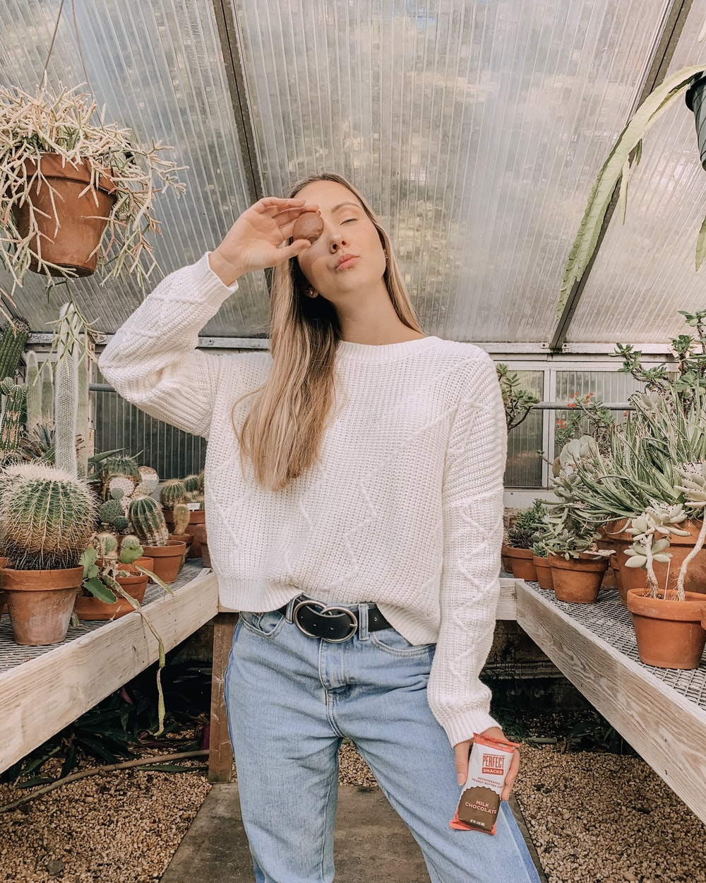 woman in white sweater and blue denim jeans standing near plants