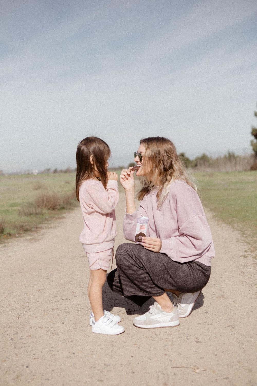 2 women sitting on brown sand during daytime